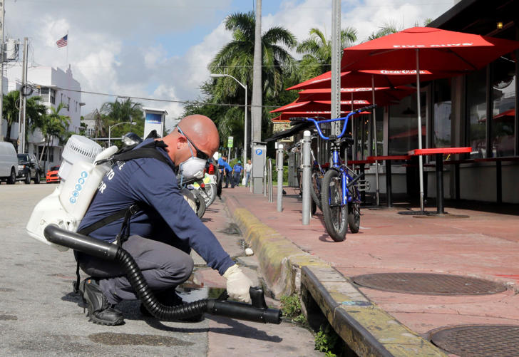 A Miami-Dade mosquito control inspector sprays a chemical mist into a storm drain pm Aug. 23, 2016, in Miami Beach, Fla.