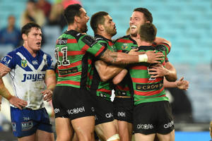 Sam Burgess of the Rabbitohs, (second right), celebrates with team mates after scoring a try