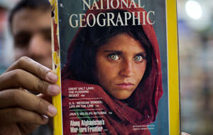 Pakistan's Inam Khan, owner of a book shop shows a copy of a magazine with the photograph of Afghan refugee woman Sharbat Gulla, from his rare collection in Islamabad, Pakistan, Wednesday, Oct. 26, 2016.