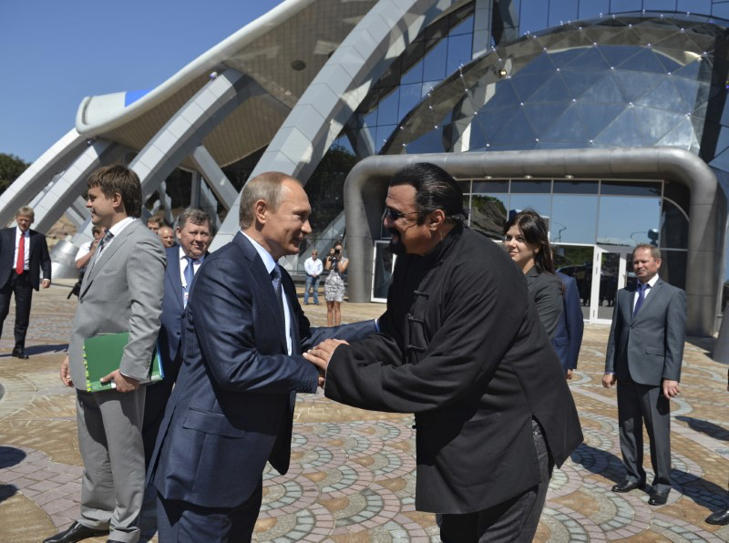 Russian President Vladimir Putin (L) shakes hands with U.S. actor Steven Seagal while visiting an oceanarium at Russky Island in the far eastern city of Vladivostok, Russia, September 4, 2015.