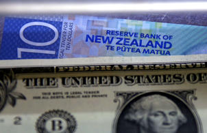 A New Zealand ten dollar note sits underneath a United States one dollar bill