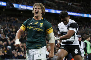 South Africa's Rohan Janse Van Rensburg celebrates after he scores a try.