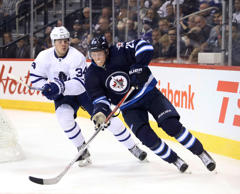 Toronto Maple Leafs center Auston Matthews (34) chases Winnipeg Jets right wing Patrik Laine (29) during the third period at MTS Centre. Winnipeg won 5-4 in overtime.