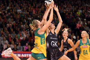 Catlin Bassett of Australia (L) contests the ball with New Zealand's Anna Harrison