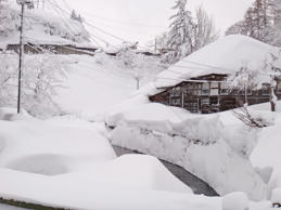 Small japanese onsen village in the winter covered with snow, river with snowdrifts in foreground: