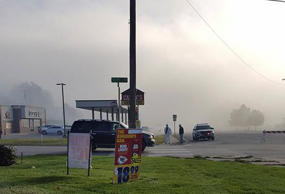 A fog believed by authorities to contain chemicals is seen near a police car after an incident in Atchison, Kan., on Friday morning.