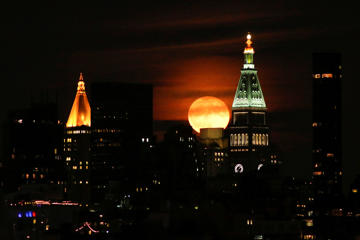 A full Hunter's super moon rises behind middle Manhattan and Empire State Building in New York City on October 16, 2016 as seen from Hoboken, NJ,