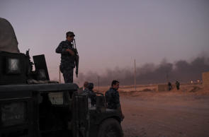 Iraqi government forces hold a position as they advance in the Qayyarah area, so...