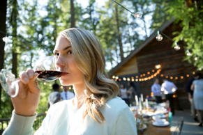 Woman drinking red wine at wedding reception