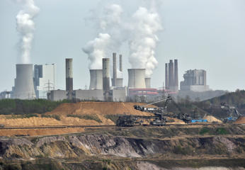 FILE - In this April 3, 2014 file photo giant machines dig for brown coal at the open-cast mining Garzweiler in front of a smoking power plant near the city of Grevenbroich in western Germany.