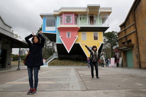 Visitors pose outside of an upside-down house created by a group of Taiwanese ar...