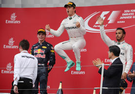 Mercedes driver Nico Rosberg, centre, of Germany celebrates on the podium after winning the Japanese Formula One Grand Prix at the Suzuka International Circuit in Suzuka, Japan, Sunday, Oct. 9, 2016. Red Bull driver Max Verstappen of the Netherlands was second and Mercedes driver Lewis Hamilton, right, of Britain third. (AP Photo/Eugene Hoshiko)