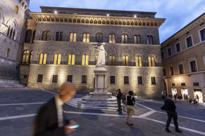 File photo: A pedestrian checks his smartphone device in Piazza Salimbeni, as the statue of Sallustio Bandini, an economist and politician, stands in front of Monte dei Paschi di Siena SpA bank headquarters in Siena, Italy.