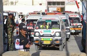 Pakistani security personnel stand guard as an ambulance carrying the coffins of attack victims drives past in Quetta on October 25, 2016.