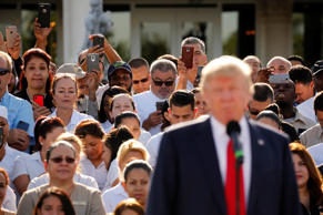 Employees of Republican U.S. presidential nominee Donald Trump stand behind him in support at a campaign event at his Trump National Doral golf club in Miami, Florida, U.S. October 25, 2016.