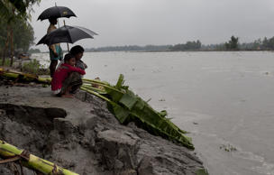 In this file photo, people look out onto a river that was a farmers crop field until September 22, 2014 in the Kalashuna village in Gaibandha district of Bangladesh. (Photo by Allison Joyce/Getty Images)