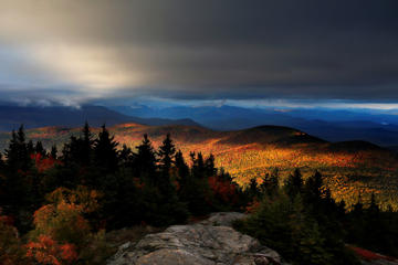 In this Tuesday, Oct. 4, 2016 photo, fall foliage colors a line of mountains in Chatham, N. H., as unsettled weather begins to clear. The state's mountain regions are approaching their peak autumn colors. (AP Photo/Robert F. Bukaty)