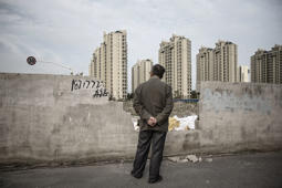 A man looks out from an opening in a wall as residential buildings stand in the distance in the Jiading district of Shanghai, China, on Monday, April 11, 2016.