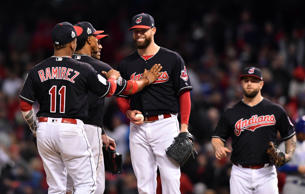 Cleveland Indians starting pitcher Corey Kluber (middle) is congratulated by teammates as he waits to be relieved in the 7th inning against the Chicago Cubs in game one of the 2016 World Series at Progressive Field.