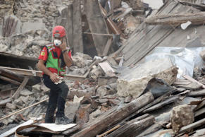 Rescuers search through debris following an earthquake in Pescara Del Tronto, Italy on August 24, 2016. (AP Photo/Andrew Medichini)