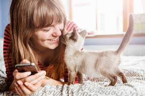 Young woman with phone gets cuddles from kitten.