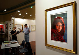 New York fine art dealer Rock Walker (2nd L) works in his booth displaying a famous portrait (R) by U.S. photographer Steve McCurry at an art fair in Sydney July 27, 2005.