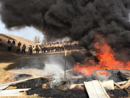 Tires burn as armed soldiers and law enforcement officers stand in formation on Thursday, Oct. 27, 2016, to force Dakota Access pipeline protesters off private land where they had camped to block construction. The pipeline is to carry oil from western North Dakota through South Dakota and Iowa to an existing pipeline in Patoka, Ill.