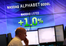 In this file photo, electronic screens post the price of Alphabet stock at the Nasdaq MarketSite in New York.