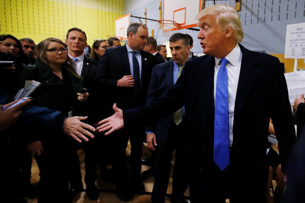 Republican presidential nominee Donald Trump shakes hands after he voted at PS 59 in New York