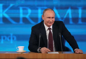 Russian President Vladimir Putin smiles as he takes part in a televised news conference in Moscow December 19, 2013.