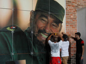 In this file photo, workers install a photograph of Cuba's former president Fidel Castro in preparation for his 90th birthday in Havana.