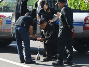 Members of police bomb disposal unit prepare a water bomb disruptor to be used to detonate a suspicious package, along Roxas boulevard near the US embassy in Manila on November 28, 2016.