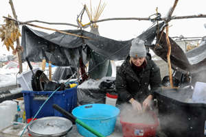 A woman washes dishes in the Oceti Sakowin camp in a snow storm during a protest against plans to pass the Dakota Access pipeline near the Standing Rock Indian Reservation, near Cannon Ball, N.D., on Nov. 28, 2016.