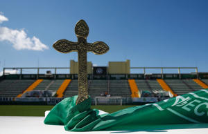 A cross is pictured over a flag of Chapecoense soccer club atop an altar prepared to a mass in tribute to their players at the Arena Conda stadium in Chapeco, Brazil November 30, 2016. REUTERS/Ricardo