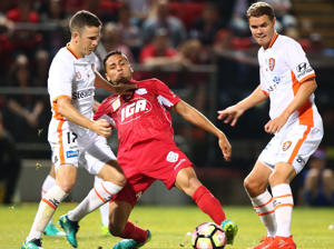 Marcelo Carrusca of Adelaide United competes for the ball with Matthew McKay of Brisbane Roar during the round six A-League match.