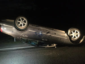 "A flipped car on State Highway 1 near Christchurch. The words ""driver out & safe"" were written on the side."
