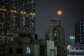 A 'supermoon' rises over residential buildings in the Kowloon district of Hong Kong on Nov. 14, 2016.