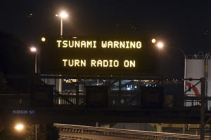 Motorway sign warning of Tsunami, in Wellington, Monday, Nov. 14, 2016, after a major earthquake struck New Zealand's south Island early Monday.