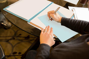 Image of someone writing on a piece of paper