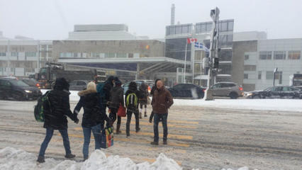Pedestrians brave the snow in Quebec City on Thursday.