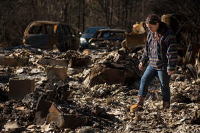 Dec 1, 2016; Gatlinburg, TN, USA; Rebecca Bell sifts through the remains of her home. Bell and her family evacuated on Monday when smoke started building up.