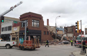Emergency crews work to clear debris from after a building collapsed in downtown...