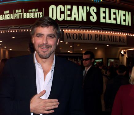 "Actor George Clooney, one of the cast members of the new film ""Ocean's Eleven"" poses with the theater marquee in background at the film's premiere December 5, 2001 in Los Angeles. The film also stars Brad Pitt and Julia Roberts and opens December 7 in the United States."