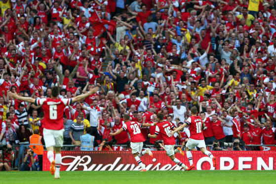 LONDON, ENGLAND - MAY 17:  Aaron Ramsey of Arsenal (16) celebrates with fans and team mates as he scores their third goal during the FA Cup with Budweiser Final match between Arsenal and Hull City at Wembley Stadium on May 17, 2014 in London, England.  (