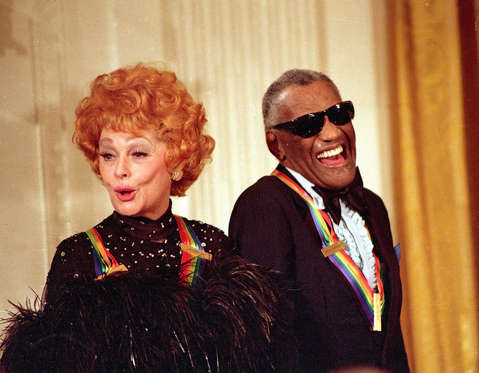 Entertainer Lucille Ball and singer Ray Charles, recipients of the Kennedy Center Honors, react during comments made by U.S. President Ronald Reagan during a tribute to the performers at the White House on Sunday, Dec. 7, 1986.