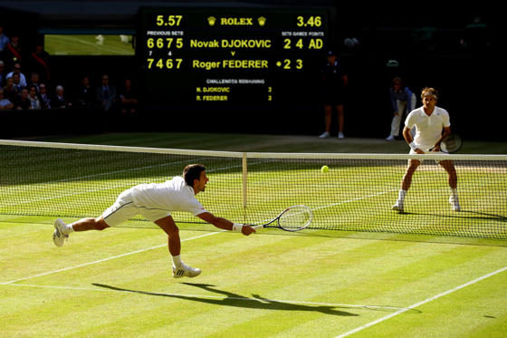 LONDON, ENGLAND - JULY 06:  Novak Djokovic of Serbia dives to make a return as Roger Federer of Switzerland stands at the net during the Gentlemen's Singles Final match on day thirteen of the Wimbledon Lawn Tennis Championships at the All England Lawn Te