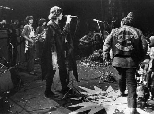 Mick Jagger sings at the Altamont Rock Festival at Livermore, Calif. on Saturday, December 6, 1969 while Hells Angels cross stage during melee to help fellow motorcyclists. The Rolling Stone hired the Hells Angels to police the concert for $500 worth of beer.