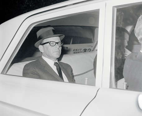 Frank Sinatra returns to the home of ex-wife, Nancy, after paying $240,000 for the safe return of his kidnapped son, Frank Jr. Sinatra is shown in back seat of FBI car. He said he had talked with Frank Jr. twice during eight telephone conversations with kidnappers in two days. The first call was to his Reno motel.