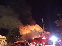 Flames rise from the top of a warehouse, which caught fire during a dance party ...