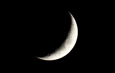 The waxing crescent moon is seen over a city center of Warsaw April 22, 2015.
